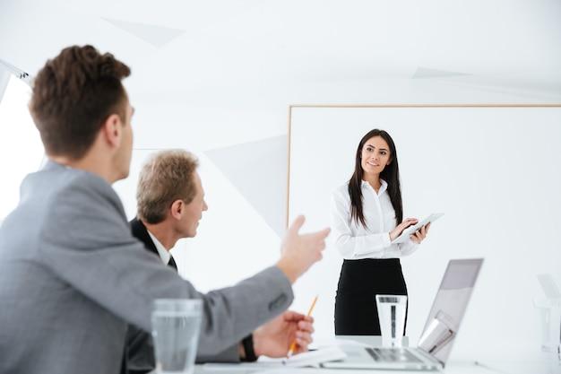Discussione del team aziendale sulla sessione nella sala conferenze in ufficio. donna in piedi vicino al tabellone.