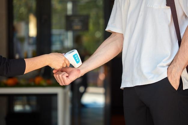 L'esperto di controllo delle malattie utilizza un termometro a infrarossi per controllare la temperatura dell'uomo
