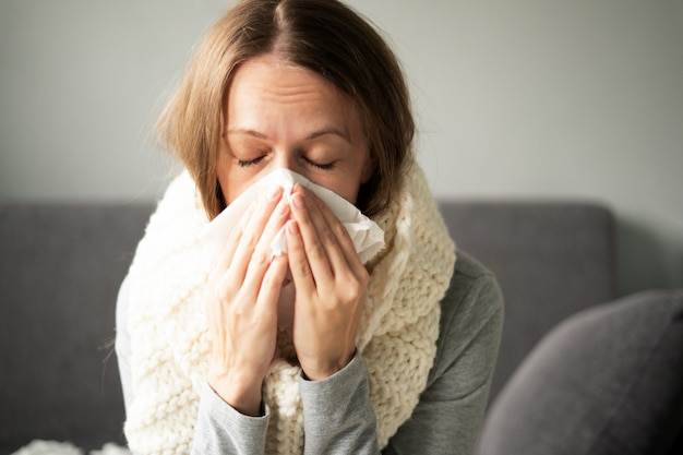Malattia. trattamento domiciliare. una donna è malata a casa, naso che cola e influenza. calorosamente vestito e coperto da una coperta.