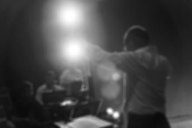 Disfocus del direttore che dirige l'orchestra sinfonica con interpreti sullo sfondo