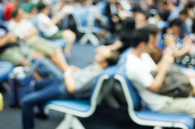 Disfocus ot persone in attesa insieme in aeroporto per la partenza dell'aereo con i bagagli