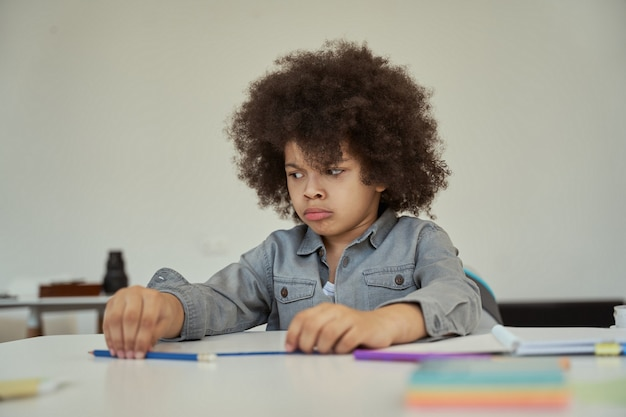 Piccolo scolaro scontento con i capelli afro che sembra triste mentre è seduto al tavolo delle elementari