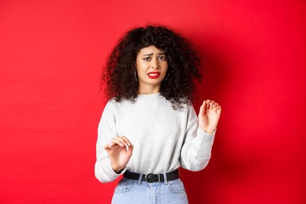 La donna disgustata e riluttante dice di no, alza le mani per bloccare o rifiutare, chiede di fermarsi, sembra a disagio, in piedi su sfondo rosso.