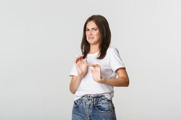 Disgustata giovane ragazza bruna che fa smorfie e mostra il gesto di arresto, rifiuta la cosa orribile e disgustosa.