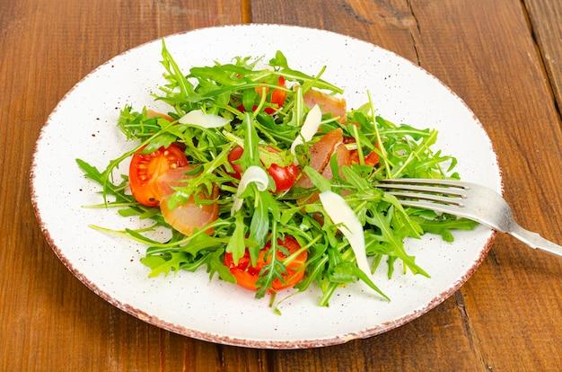Piatto di rucola pomodori di carne secca e formaggio insalata sul piatto su legno