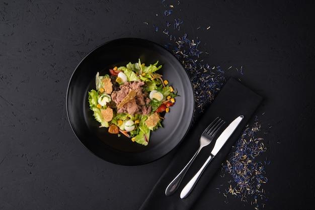 Un piatto di carne bollita su una superficie di legno nera, vista dall'alto