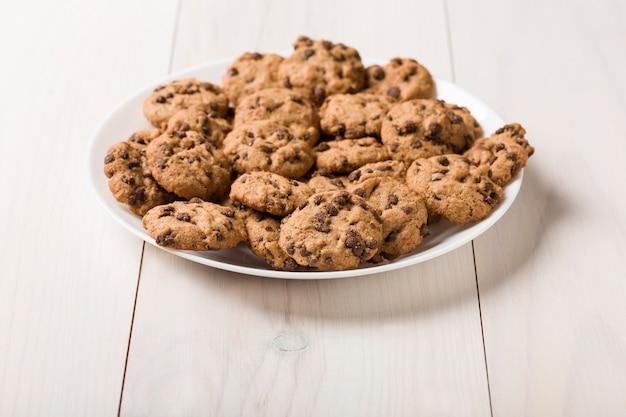 Piatto di biscotti artigianali senza glutine con pepite di cioccolato su fondo di legno bianco