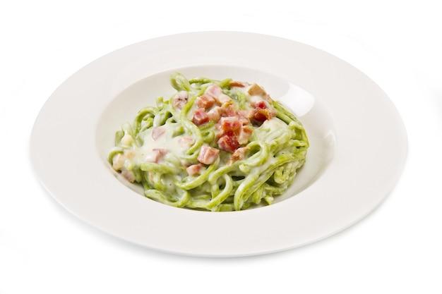 Piatto di spaghetti verdi con pancetta e panna