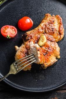 Piatto di braciola di maiale alla griglia con pomodori vista dall'alto con coltello e fetta sulla forcella