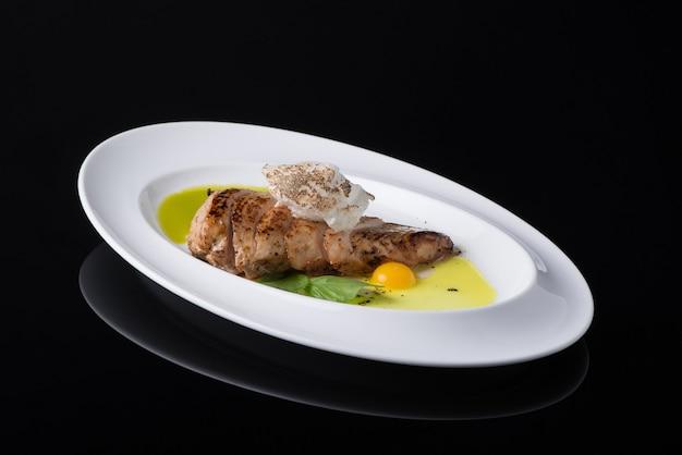 Piatto di carne con l'uovo in un piatto, su un fondo nero, isolato