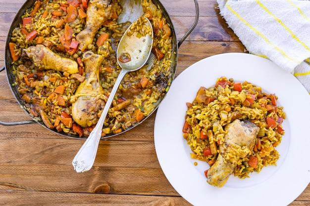 Piatto servito con una porzione di riso classico con pollo e zafferano o paella di pollo e la paella con il cucchiaio a lato. cibo tipico spagnolo. Foto Premium