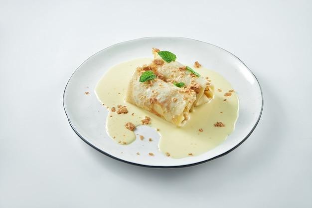 Un piatto di cucina ucraina - frittelle ripiene di ricotta con salsa cremosa dolce su un piatto bianco su un piatto bianco. blini o crepes francesi