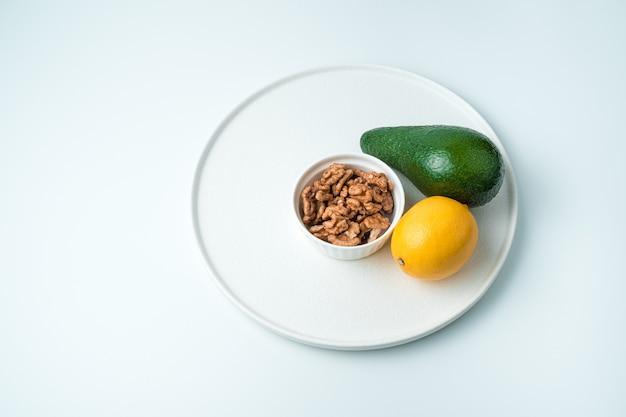 Piatto con avocado, limone e noci in un piatto su una superficie bianca