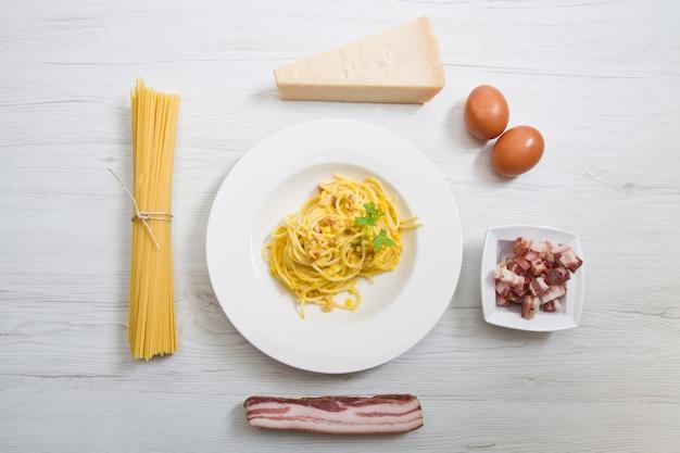 Piatto con spaghetti alla carbonara e ingredienti su legno bianco Foto Premium