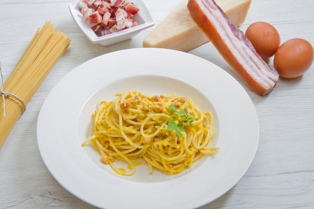 Piatto con spaghetti alla carbonara e ingredienti su legno bianco
