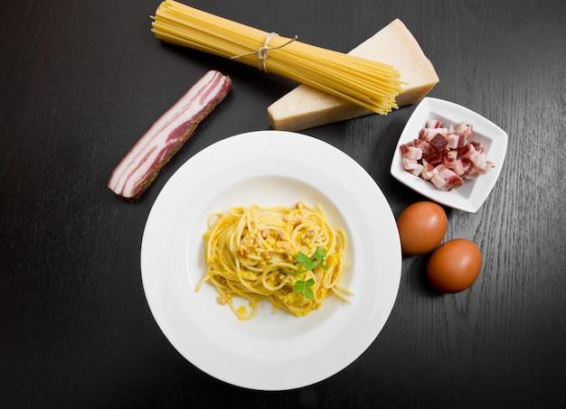 Piatto con spaghetti e ingredienti alla carbonara