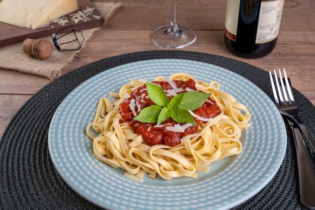 Piatto con le tagliatelle condite con salsa di pomodoro, con un bicchiere di vino rosso frizzante.