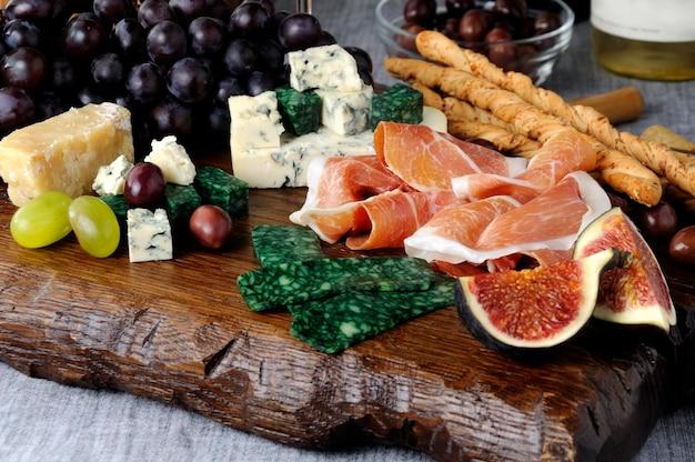 Piatti per antipasto su una tavola di legno con prosciutto diversi tipi di formaggio uva e fichi