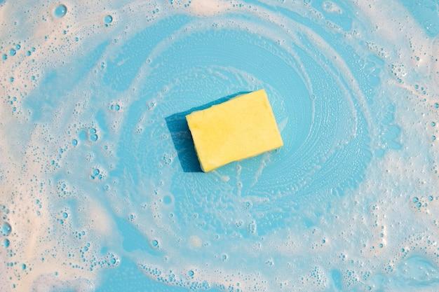 Spugna per stoviglie con schiuma sulla superficie blu