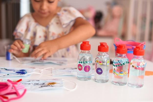 Barattoli di gel disinfettante per bambini con una ragazza sullo sfondo. messa a fuoco selettiva