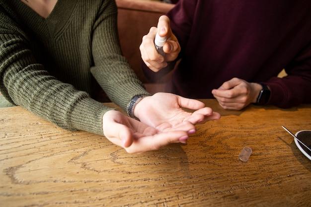 Disinfezione delle mani applicando spray alcolico o spray antibatterico per prevenire la diffusione di germi
