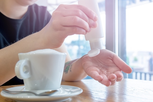 Disinfezione delle mani. assunzione di gel disinfettante alcolico sulle mani in luce bianca per prevenire l'epidemia di virus. il disinfettante per le mani previene l'infezione da virus e peste, previene il virus covid-19