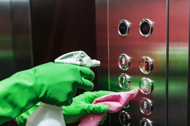 Disinfezione dell'ascensore con un disinfettante e un tovagliolo