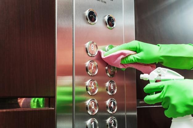 Disinfezione dell'ascensore con un disinfettante e un tovagliolo Foto Premium