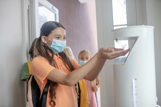 Disinfezione. ragazza in maschera preventiva che ottiene un disinfettante in mano