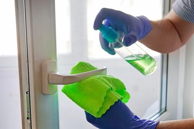 Disinfezione dei locali. prevenzione coronavirus, malattie infettive. mettere in ordine. lavaggio vetri. l'uomo disinfetta la maniglia della porta con liquido disinfettante. spruzzare la maniglia della porta e pulire con un panno.