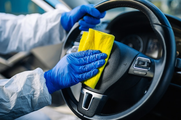 Il professionista della disinfezione pulisce il volante di un'auto