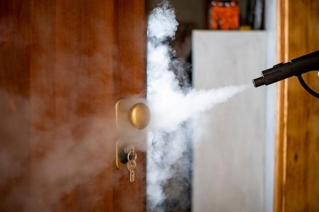 Disinfezione e sanificazione con vapore a casa, il flusso di vapore è diretto alla maniglia della porta e alle chiavi nella serratura