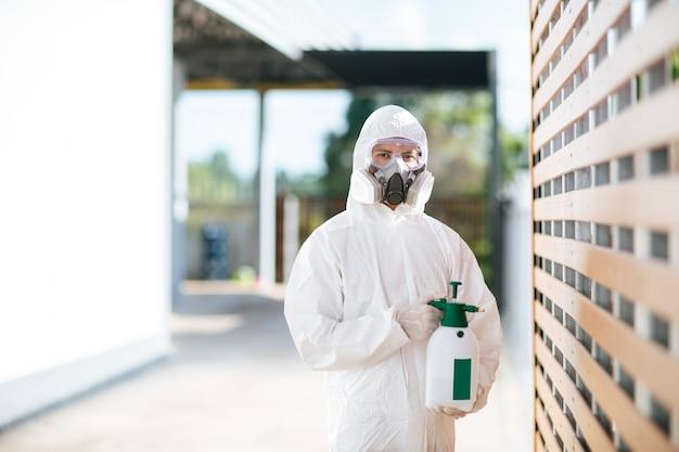 Personale specializzato nella disinfezione in tuta di dispositivi di protezione individuale (dpi), guanti, maschera e visiera, pulizia dell'area di quarantena con una bottiglia di disinfettante spray pressurizzato per rimuovere covid-19