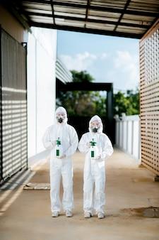 Team di specialisti della disinfezione in tuta di dispositivi di protezione individuale (dpi), guanti, maschera e visiera, pulizia dell'area di quarantena con una bottiglia di disinfettante spray pressurizzato per rimuovere covid-19
