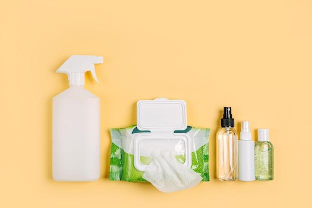 Spray disinfettante con salviettine umidificate antibatteriche e disinfettante per le mani su sfondo giallo. prodotto per l'igiene personale per protezione virus, influenza, coronavirus, covid-19