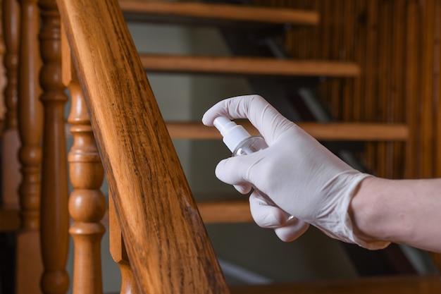 Disinfezione della ringhiera delle scale. pulizia profonda per la prevenzione delle malattie covid-19. alcool, spray disinfettante su salviette di balaustro in casa per sicurezza, infezione del virus covid-19