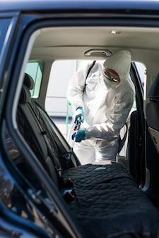 Il disinfettante in una tuta protettiva conduce la disinfezione nell'area contaminata dell'auto per prevenire il coronavirus. assistenza sanitaria.