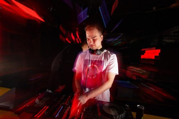 Il disc jockey guida la folla. l'uomo sfocato in maglietta bianca e cuffie mescola le tracce con i giradischi. rave in discoteca. concetto di vita notturna. interno del club sfocato con luci rosse.