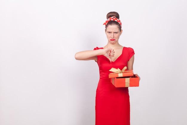 Non mi piace. la donna che tiene la scatola rossa e dimostra il pollice verso il basso. indoor, girato in studio, isolato su sfondo grigio