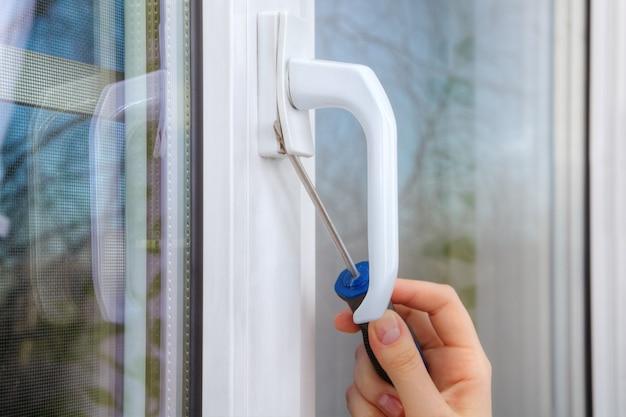 Smontare la maniglia sulla finestra in pvc utilizzando un cacciavite, mano ravvicinata con lo strumento.