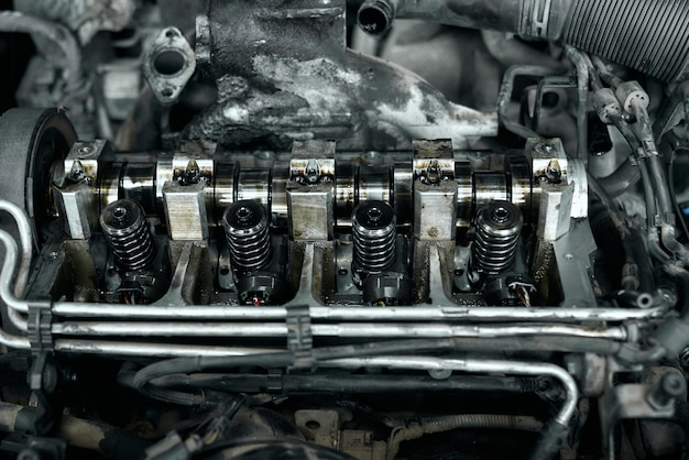 Motore di automobile smantellato sotto il cofano con dettagli sporchi