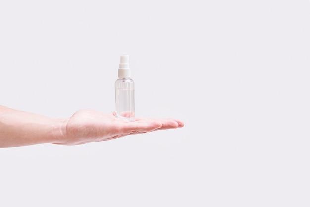 Dispenser con un disinfettore in mano su grigio