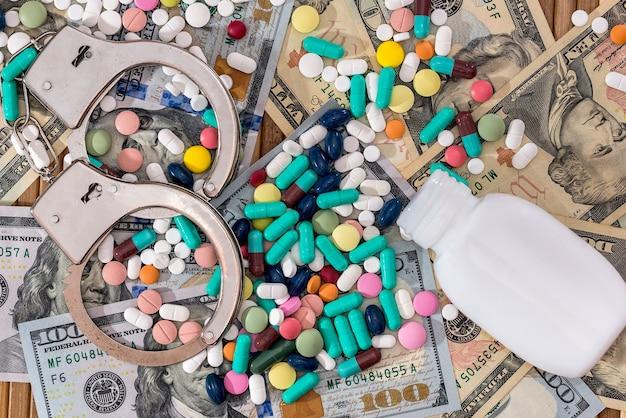 Pillole disperse dal contenitore con le manette sulle banconote in dollari