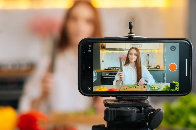 Visualizzazione del video blog di registrazione della fotocamera per la donna blogger alimentare che taglia la verdura nella cucina moderna