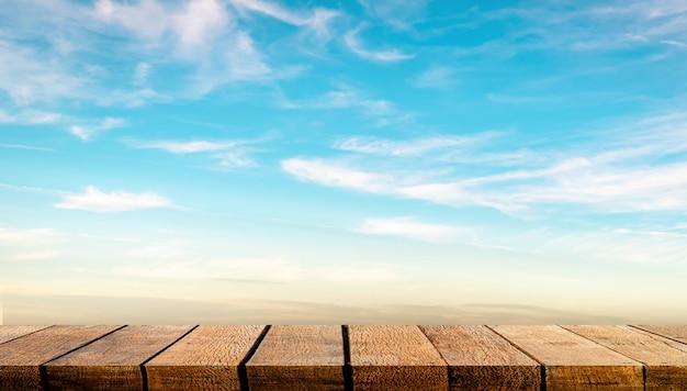 Visualizzi il contatore della tavola dello scaffale del bordo di legno con lo spazio della copia per il contesto e il fondo di pubblicità con il fondo blu del cielo della radura della nuvola