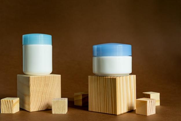 Mostra podio in legno con barattoli di crema su uno sfondo marrone. contenitori per la cura del viso. mockup di cosmetici. prodotti giorno e notte