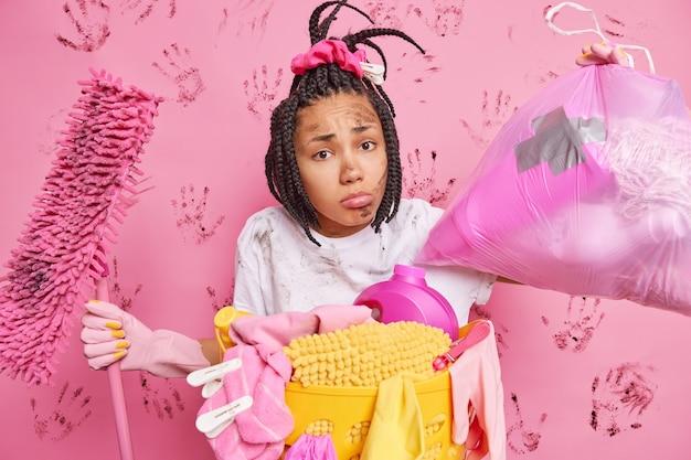 La donna afroamericana dispiaciuta con i dreadlocks trasporta il sacchetto della spazzatura tiene le pose del mocio vicino al cesto della biancheria sporchi dà consigli per la pulizia occupata a fare i lavori domestici durante il fine settimana