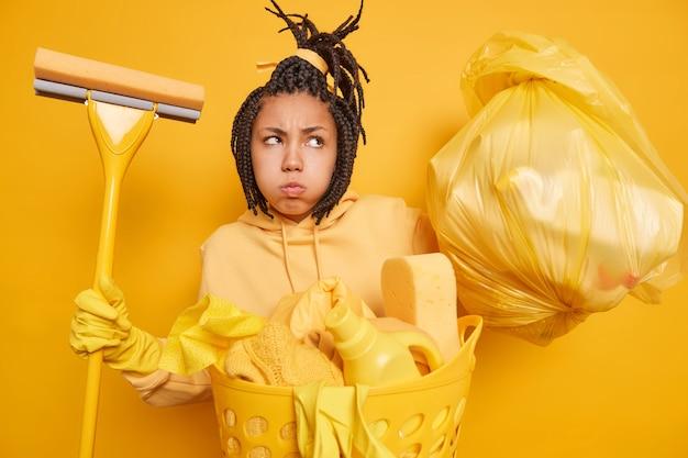 Una donna dispiaciuta dalla pelle scura con le trecce che soffia sulle guance fa una smorfia infelice tiene il sacco della spazzatura