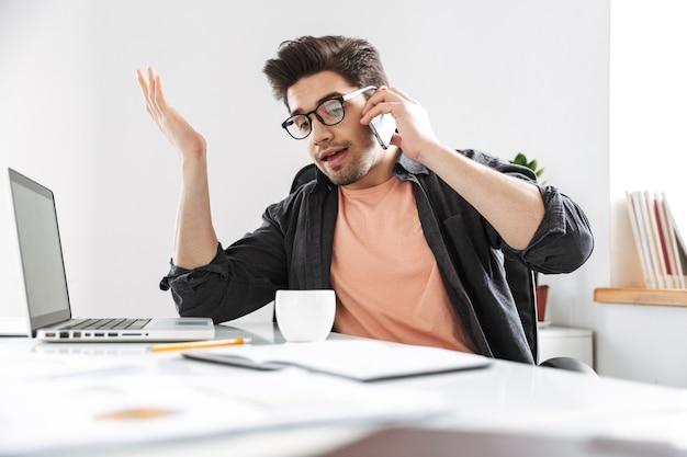 Un bell'uomo dispiaciuto con gli occhiali che parla con lo smartphone mentre lavora al tavolo in ufficio