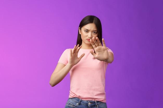 Ragazza asiatica riluttante intensa dispiaciuta che blocca, cerca di proteggere il viso, alza le mani, fermati, gesto di divieto, imbronciato accigliato, rifiutando l'offerta fastidiosa, stando sullo sfondo viola, rifiutando